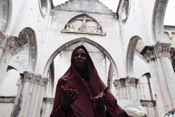 A displaced woman prayed Friday inside a war-ravaged Cathedral in Mogadishu, Somalia. (Feisal Omar/Reuters)